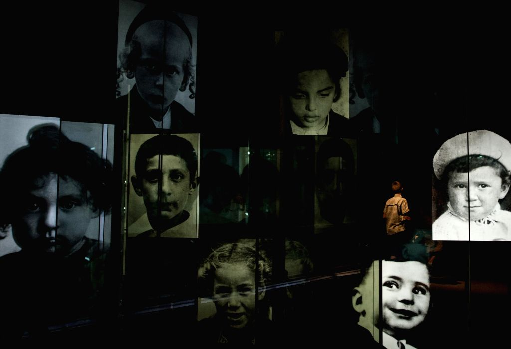 A visitor walks past photographs of Holocaust children victims at Children's Memorial of the Yad Vahsem Holocaust memorial museum in Jerusalem, on April 28, ...