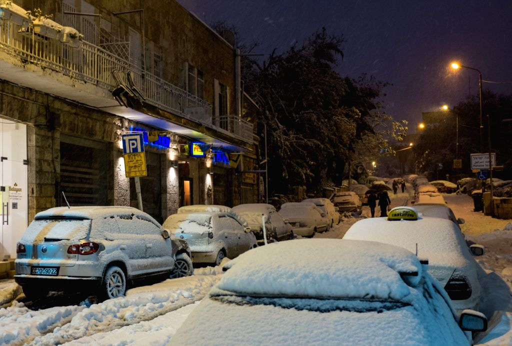 Pedestrians walk past a snow-covered street in Jerusalem, on Dec. 13, 2013. A heavy storm in Israel, ongoing for three days straight, has paralyzed the ...