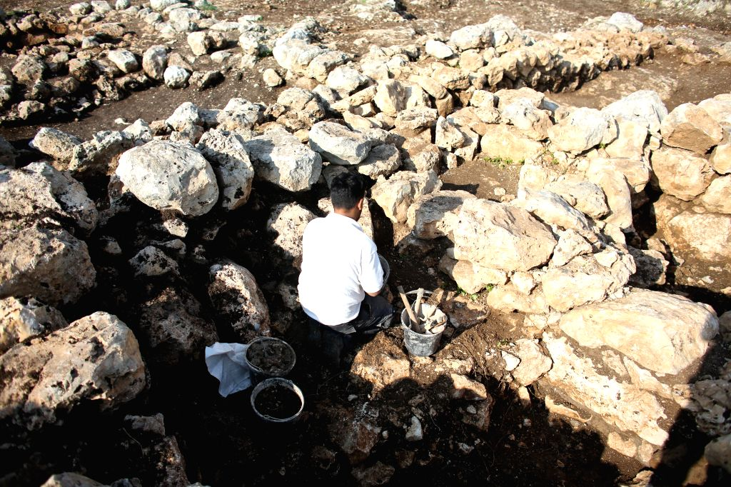 An Israeli archaeologist works on the excavation site of a 2,800-year-old farmhouse in the the city of Rosh HaAyin, central Israel, on Dec. 16, 2014. Israel's ...