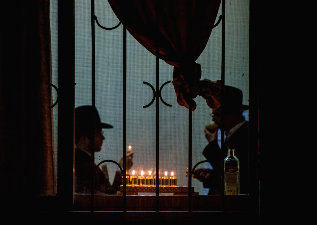 An ultra-Orthodox Jewish man lights candles to mark the seventh night of Hanukkah at his home at Mea Shearim in Jerusalem, on Dec. 22, 2014. Hanukkah, also known .