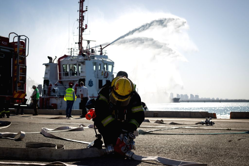 An Israeli fire fighter attends a rescue drill at Ashdod port, southern Israel, on Dec. 29, 2014. The rescue drill, regularly practiced as a scenario, was based ..