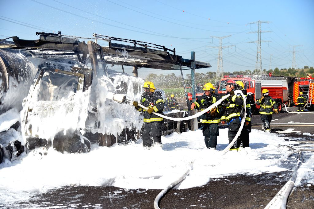 Firefighters work on the scene where a man was killed during explosions from a gas tanker truck which caught fire on the Jerusalem-Tel Aviv Highway, after an accident in which it hit a ...