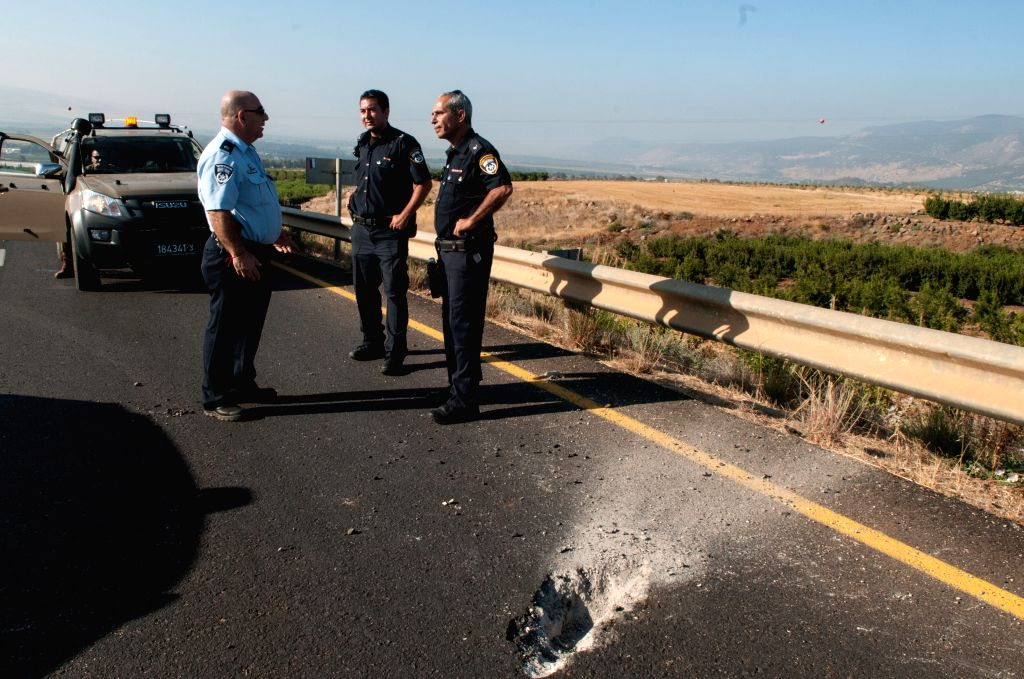 Israeli security forces stand next to damage caused by Katyusha style rocket fired from Lebanon near the border between northern Israel and Lebanon, on July 11, ..