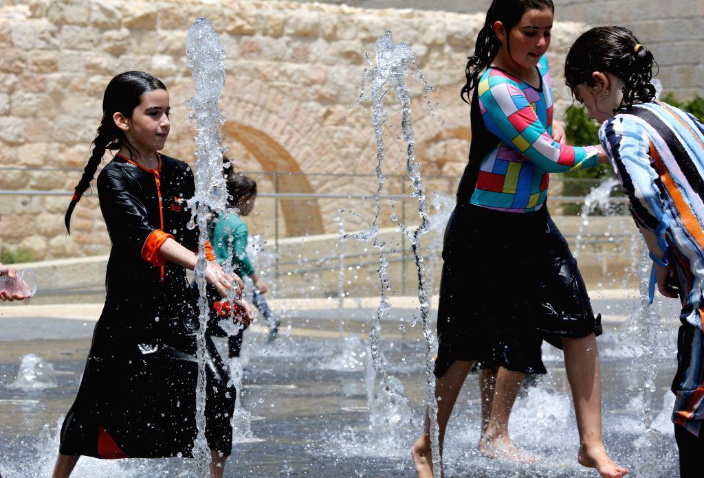 JERUSALEM, July 17, 2019 - Children play at a fountain in central Jerusalem on July 17, 2019. A heatwave hit Jerusalem recently.