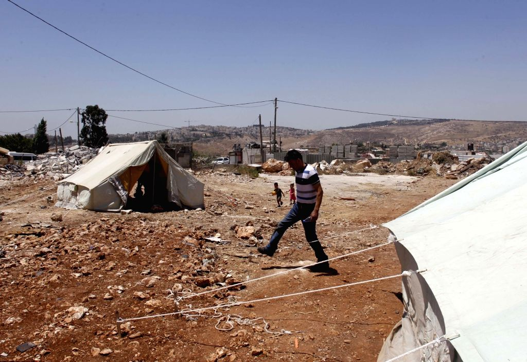 JERUSALEM, July 19, 2018 - A Palestinian walks beside a tent near the ruins of houses in the East Jerusalem neighbourhood of Beit Hanina, July 19, 2018. Palestinian residents demolished their ...
