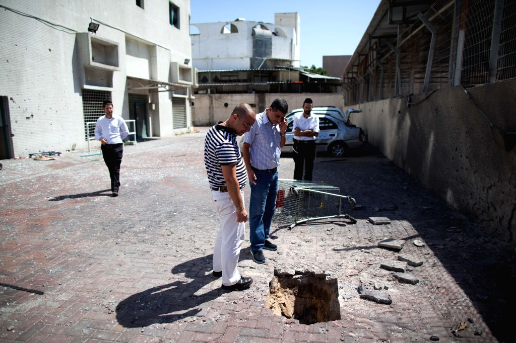 Israelis look at a hole hit by a rocket fired from the Gaza Strip near a shop in Ashdod, southern Israel, on July 9, 2014. Since Israel launched operation ...
