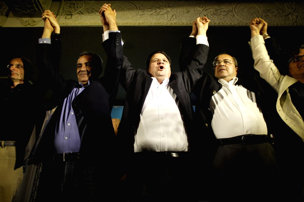 Head of Israel's Joint Arab List Ayman Odeh (C), reacts with members of the party after exit poll results in Nazareth, Israel, on March 17, 2015. According to ...