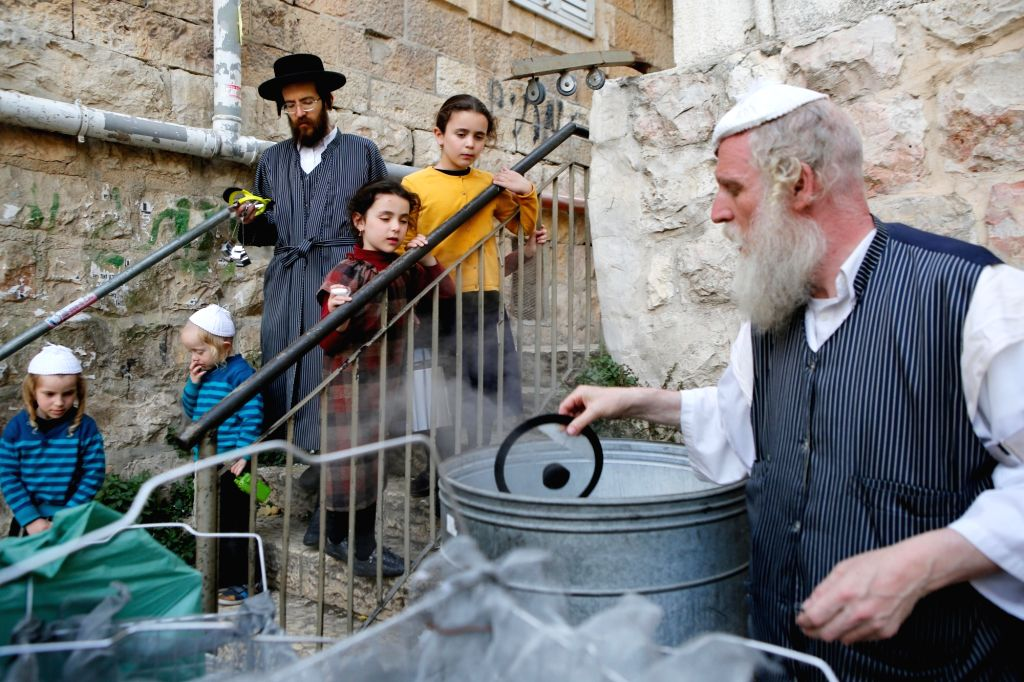 JERUSALEM, March 28, 2018 - An ultra-Orthodox Jewish man dips his cooking utensil in boiling water to remove remains of leaven as he prepares for the Jewish holiday of Passover in Jerusalem's Mea ...