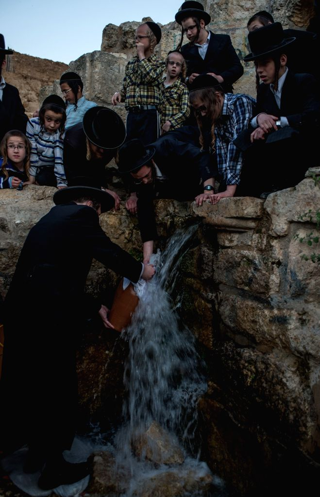 "Ultra-Orthodox Jews collect spring water during the sunset for the traditional Jewish rite of ""Mayim Shelanu"" (water which has ""slept"") ..."
