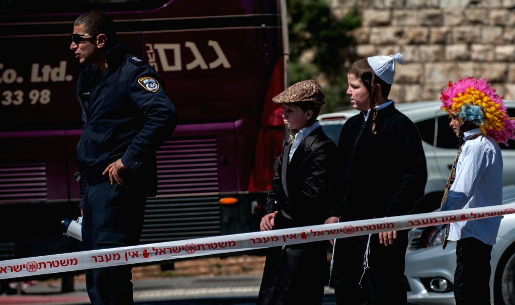 Dressed-up Jewish teenagers look at the site where an attack occurred in east Jerusalem, on March 6, 2015. At least five people, including four Israeli female ...