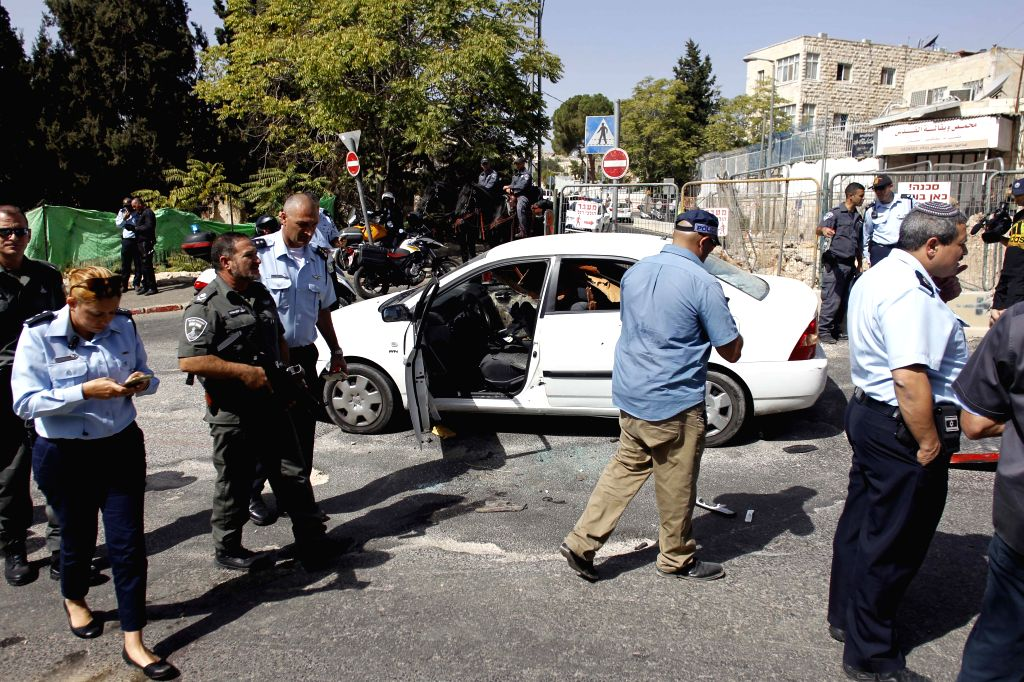 JERUSALEM, Oct. 9, 2016 - Israeli police check the gunman's car at the site of a shooting attack near Ammunition Hill light rail station in Jerusalem, Oct. 9, 2016. Two Israelis were killed and five ...