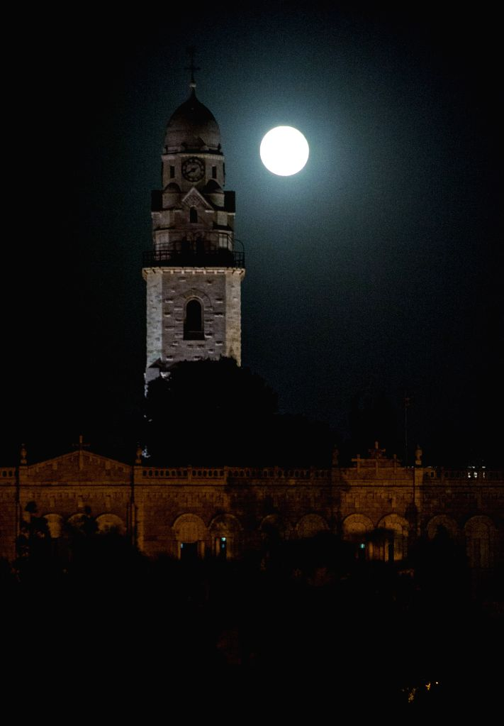 A full moon rises over the Bell Tower of the Church of the Dormition on Mount Zion in the Old City of Jerusalem, on Sept. 9, 2014.