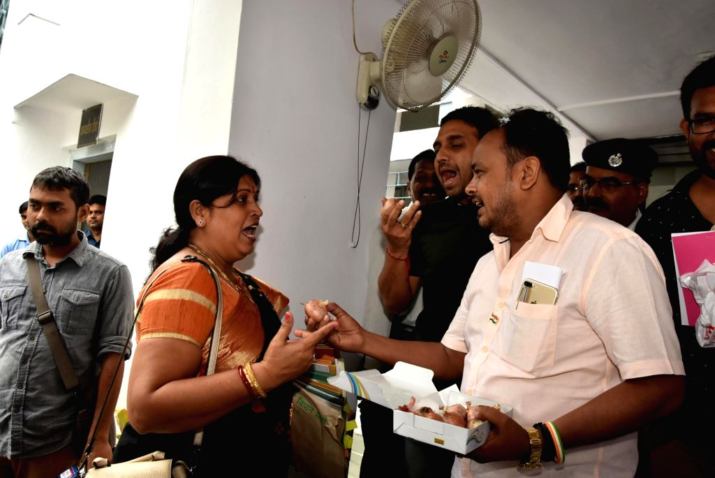 Jharkhand Mukti Morcha (JMM) and opposition party MLAs offer onions to NDA MLAs protesting price rise on the last day of the monsoon session outside Jharkhand Assembly in Ranchi on Aug 12, ...