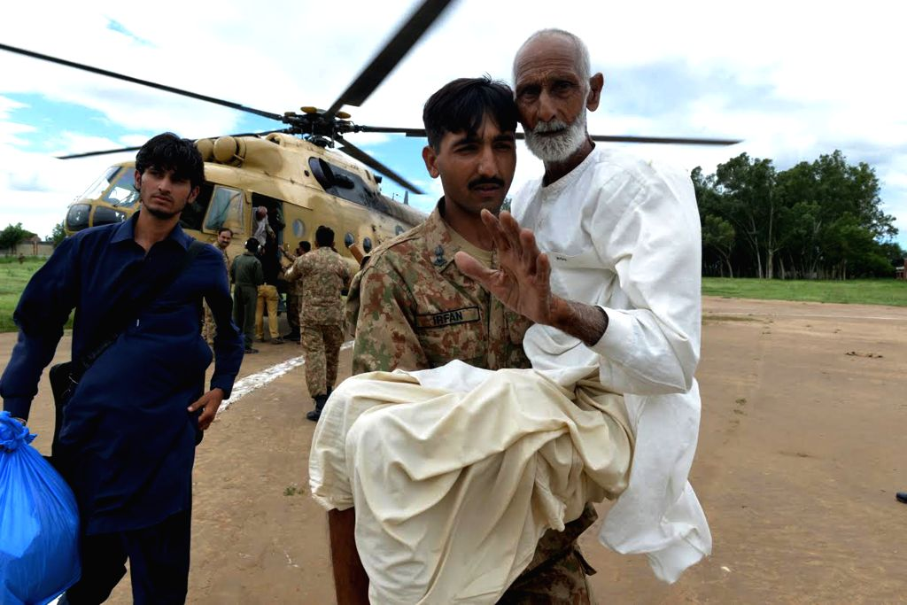 Photo released by Pakistan's Inter Services Public Relations (ISPR) on Sept. 7, 2014, shows a Pakistani army soldier carrying an elderly man after rescuing him from .