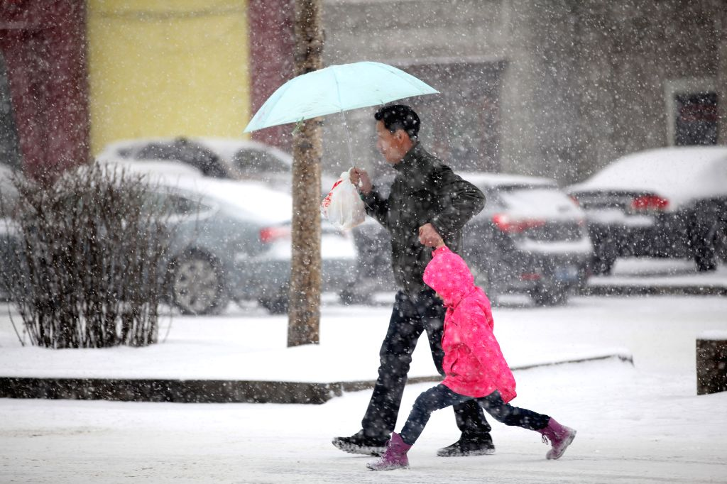 A parent and his child brave snow as they walk on a street in Jilin City, northeast China's Jilin Province, March 8, 2015. A snowstorm hit central and southern part ...