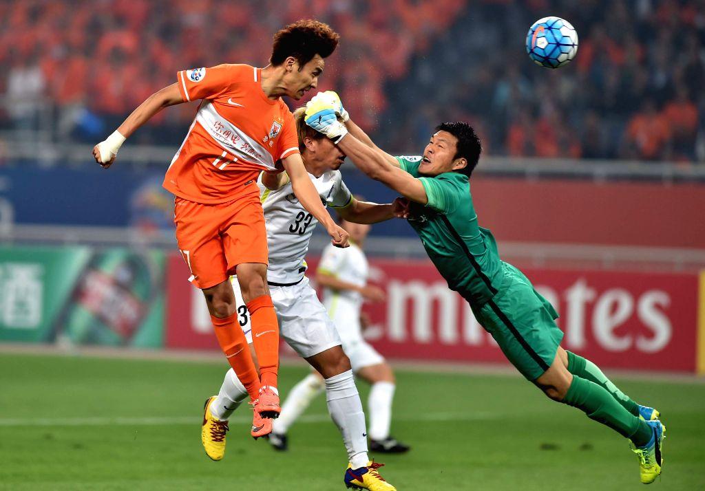JINAN, April 20, 2016 - Wu Xinghan (L) of China's Shandong Luneng FC heads for the ball while Hayashi Takuto (R), goalkeeper of Japan's Sanfrecce Hiroshima, saves the ball but hit his teammate ...