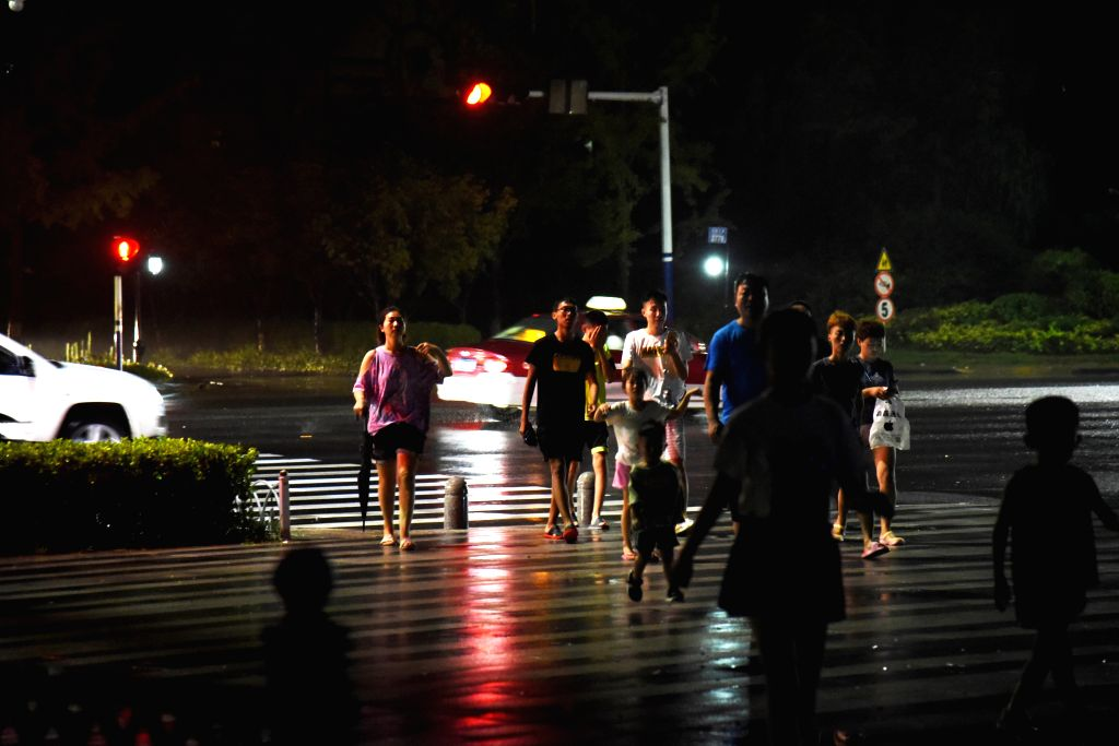 JINAN, Aug. 11, 2019 - People walk near the coast in Huangdao district of Qingdao, east China's Shandong Province, Aug. 11, 2019. Typhoon Lekima makes its second landing at 8:50 p.m. on Sunday on the ...