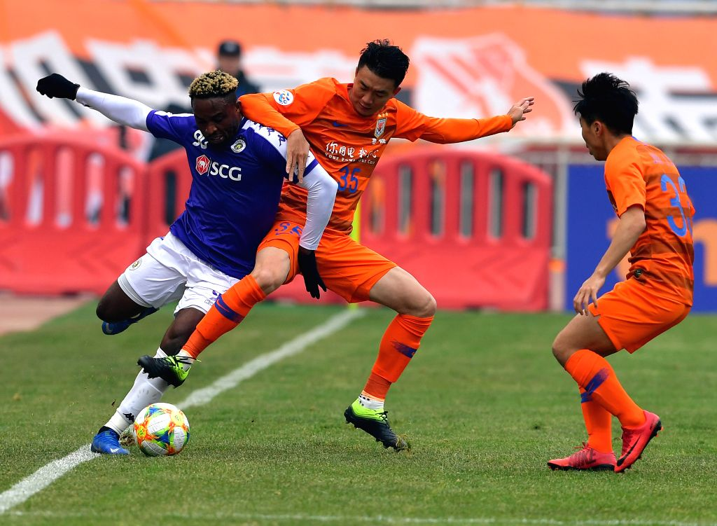 JINAN, Feb. 19, 2019 - Hanoi FC's Pape Omar Faye (L) shoots during the play-off stage match between China's Shandong Luneng and Vietnam's Hanoi FC of the AFC Champions League in Jinan, capital of ...