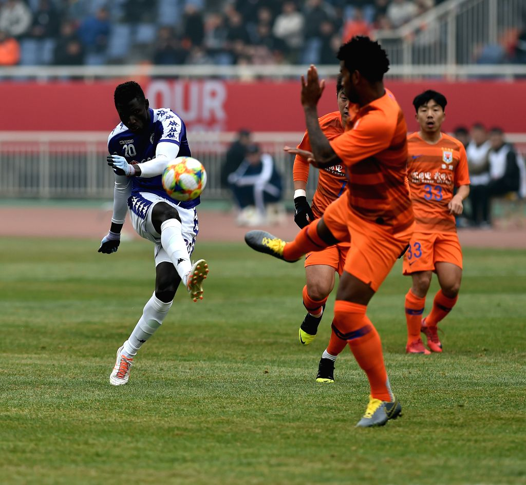 JINAN, Feb. 19, 2019 - Shandong Luneng's Dai Lin (C) vies with Hanoi FC's Ganiyu Bolaji Oseni (L) during the play-off stage match between China's Shandong Luneng and Vietnam's Hanoi FC of the AFC ...