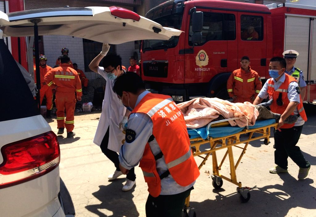 JINAN, May 27, 2017 - Rescuers transfer an injured person at the building collapse site in Shizhong District of Jinan, capital of east China's Shandong Province, May 27, 2017. Six people were killed ...