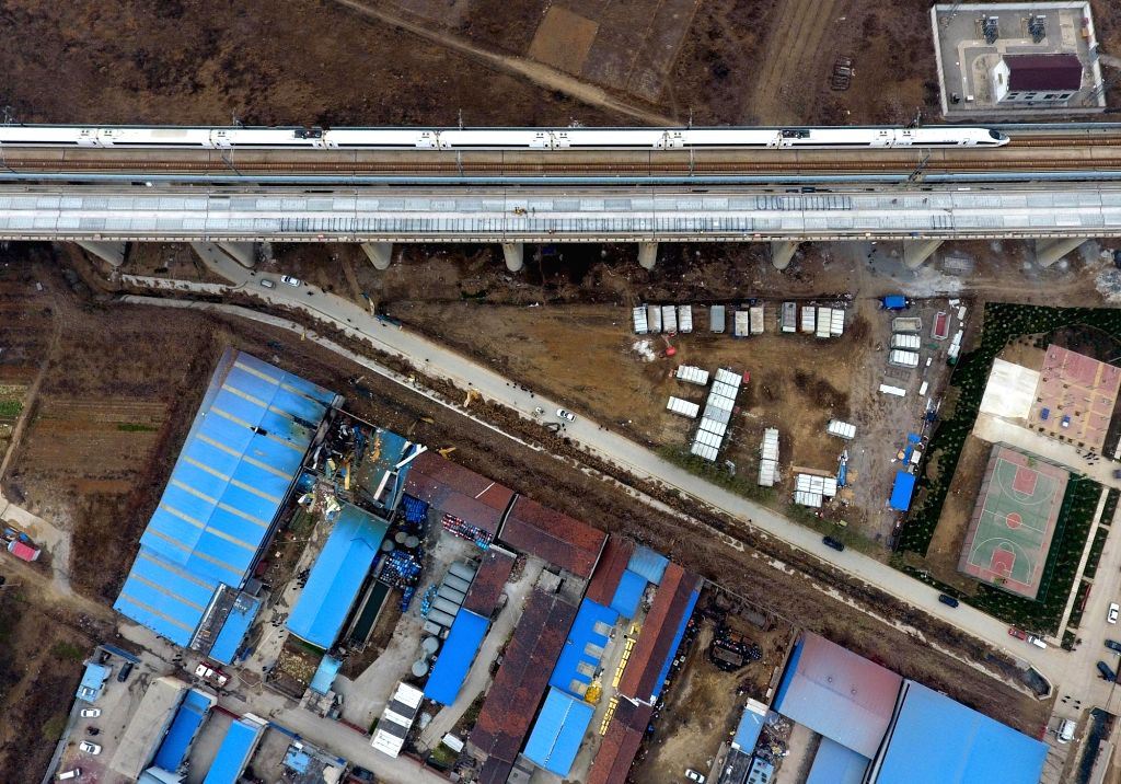 JINAN, Nov. 29, 2016 - A bullet train runs on the Beijing-Shanghai high-speed rail nearby a blast accident site at a concrete additive plant in Jinan City, capital of east China's Shandong Province, ...
