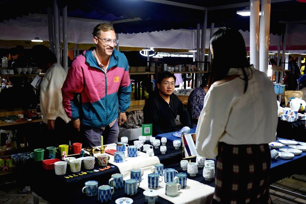JINGDEZHEN, Oct. 18, 2019 - An artist talks with a customer during a porcelain fair in Jingdezhen, east China's Jiangxi Province, Oct. 17, 2019. An autumn porcelain fair opened Thursday in ...