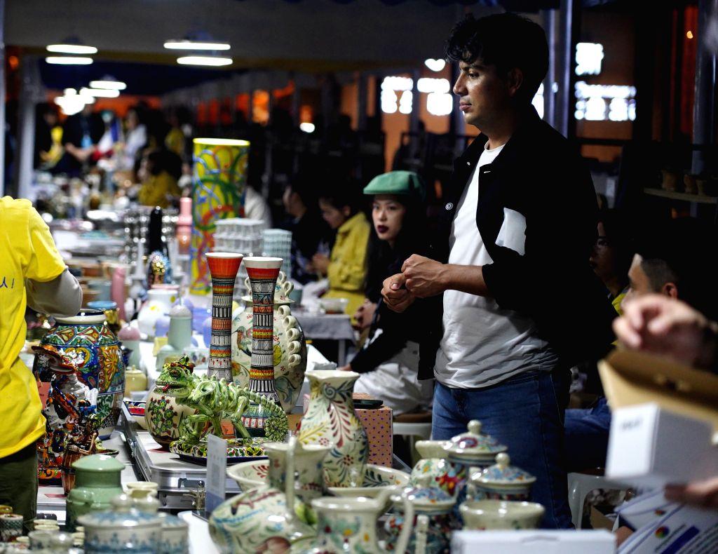 JINGDEZHEN, Oct. 18, 2019 - Artists display porcelain works during a porcelain fair in Jingdezhen, east China's Jiangxi Province, Oct. 17, 2019. An autumn porcelain fair opened Thursday in ...