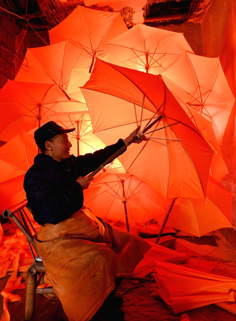 JINGXIAN, Nov. 29, 2016 - A worker checks the newly-made oilcloth umbrellas in Gufeng Village of Jingxian County, east China's Anhui Province, Nov. 29, 2016. The umbrella, made of oiled cloth and ...