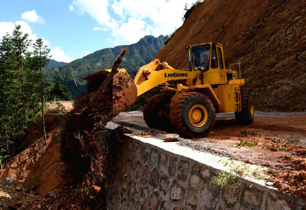 JINXIU, Sept. 19, 2018 - A worker clears a road damaged by Typhoon Mangkhut in Liuxiang Village of the Yao Autonomous County of Jinxiu in south China's Guangxi Zhuang Autonomous Region, Sept. 19, ...