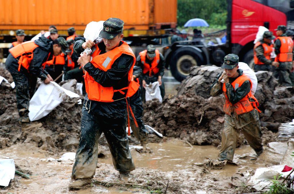 JIUJIANG, July 4, 2016 - Soldiers carry sandbags to reinforce the dyke of Saicheng Lake in Jiujiang City, east China's Jiangxi Province, July 4, 2016. Due to rapid rise of Saicheng Lake's water ...