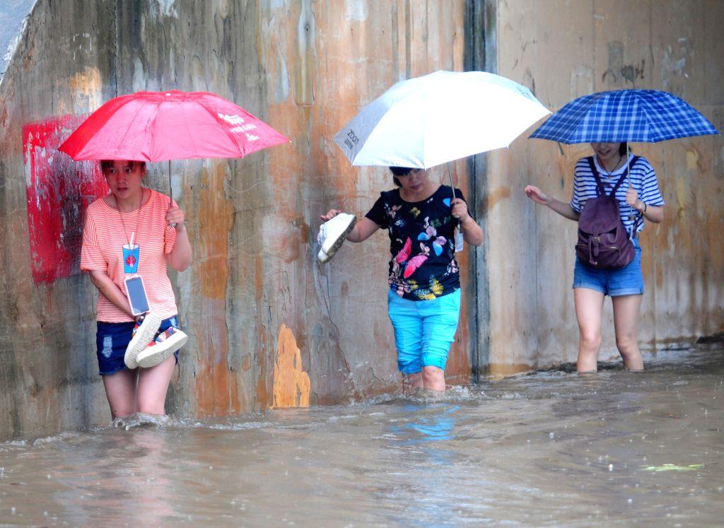 JIUJIANG, June 1, 2016 - Pedestrians walk on a flooded street in Jiujiang, east China's Jiangxi Province, June 1, 2016. Torrential rain hit the city and caused flood.