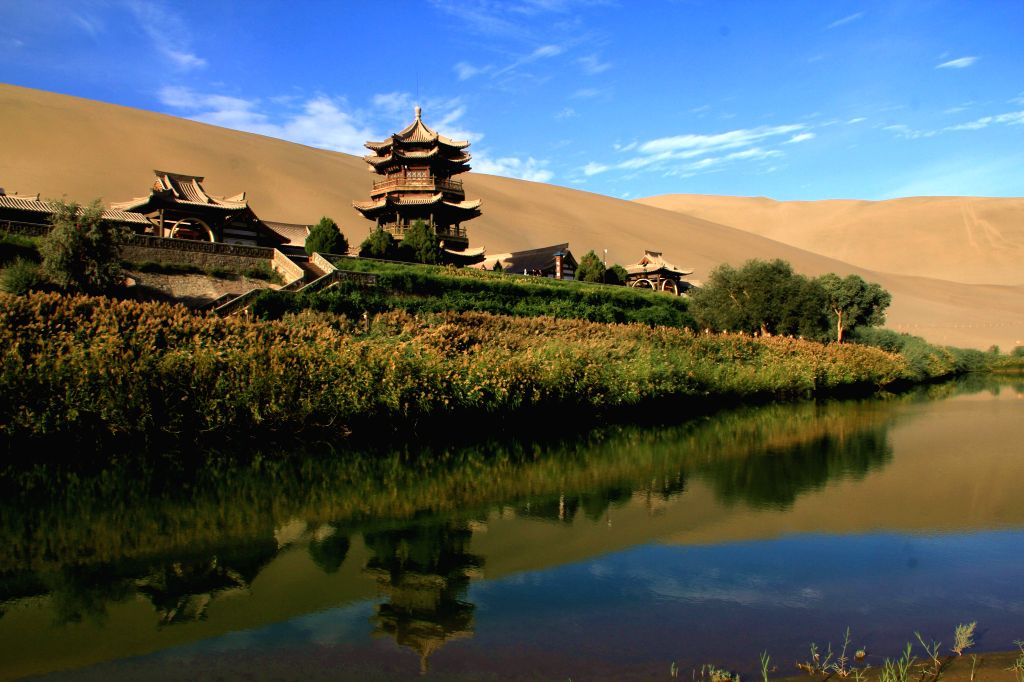 Photo taken on Sept. 7, 2014 shows scenery of Yueya Spring (Crescent Spring) and the adjacent Mingsha Mountain Dunes (Singing-Sand Dunes) coexisting in Dunhuang ...