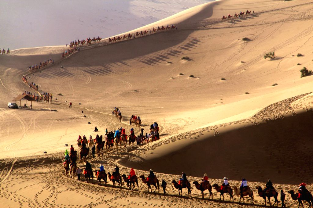 Tourists ride camels to view the scenery of Yueya Spring (Crescent Spring) and the adjacent Mingsha Mountain Dunes (Singing-Sand Dunes) in Dunhuang City, northwest .