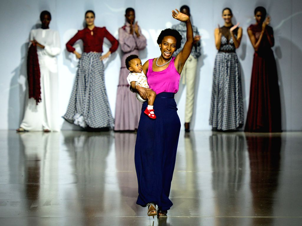 JOHANNESBURG, March 12, 2016 - Local designer Khomotjo Malatji of Grapevine greets the audience with her child after presentation of her creations on the third day of Mercedes-Benz Fashion Week ...