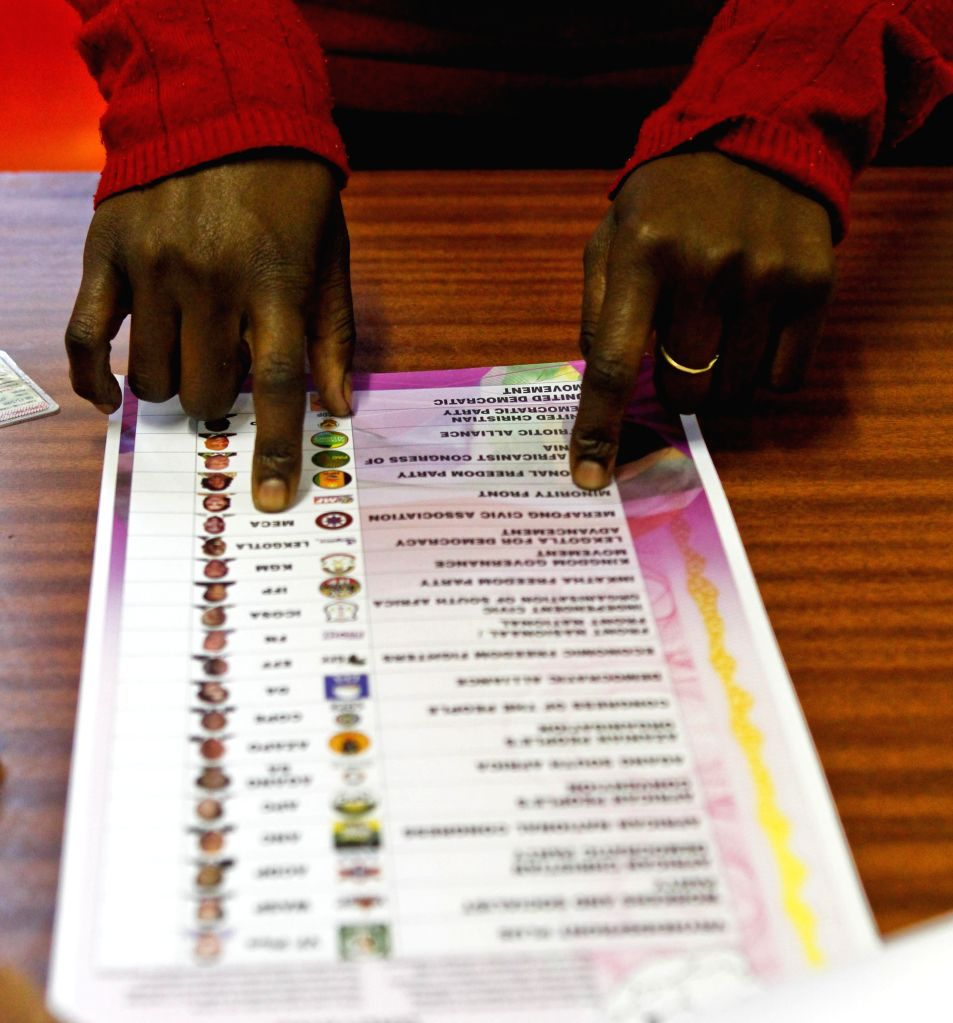 A staff member of a polling station at Orlando West High School shows a sample ballot in Soweto, Johannesburg, South Africa, May 6, 2014. According to South ...