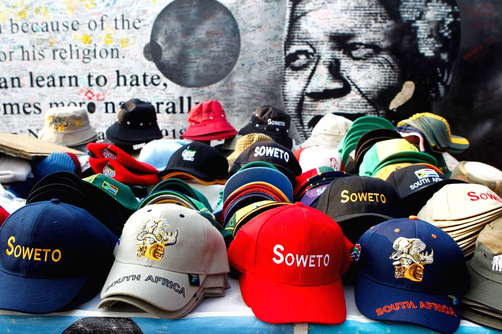 Photo taken on May 6, 2014 shows souvenirs on display in front of a poster of late South African President Nelson Mandela, in Soweto, Johannesburg, South Africa.
