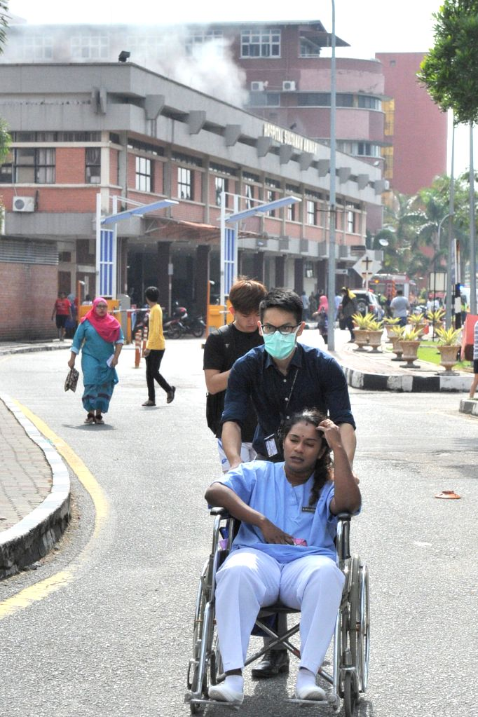 JOHOR BAHRU, Oct. 25, 2016 - Staff evacuate a patient after a fire broke out at a hospital in Johor Bahru in southern Malaysia on Oct. 25, 2016. A fire that broke out at a hospital in Johor Bahru in ...