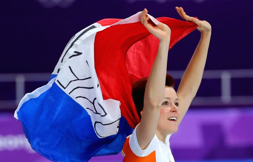 Jorien ter Mors of the Netherlands carries her country's national flag as she makes a victory lap after winning the gold in the women's 1,000-meter speed skating race at PyeongChang Winter ...