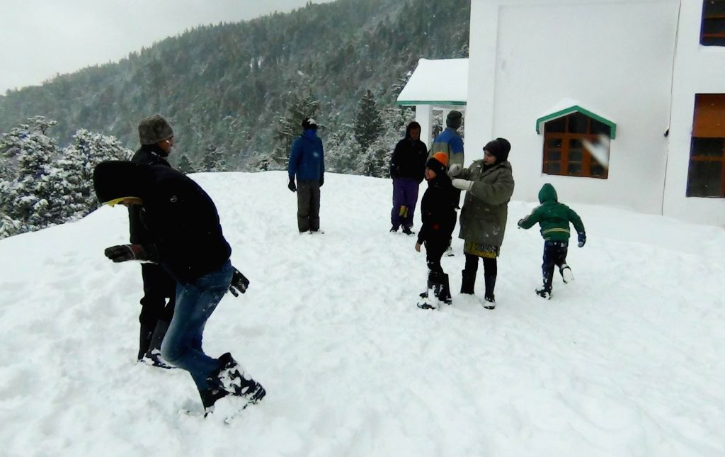 Tourists enjoy themselves at Joshimath after fresh snowfall on Jan 14, 2015.