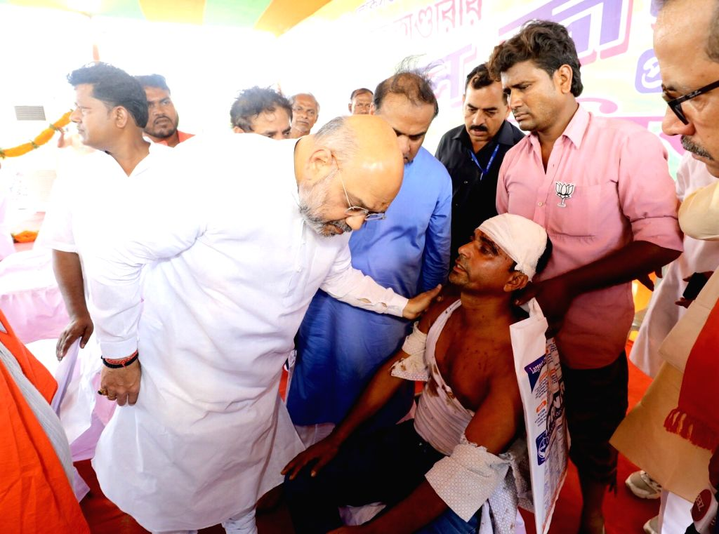 Joynagar: BJP chief Amit Shah meets party worker Shribas Gayen who sustained injuries after being allegedly attacked by miscreants backed by the Trinamool Congress when voting was underway on Sunday for the sixth phase of 2019 Lok Sabha elections; in - Amit Shah