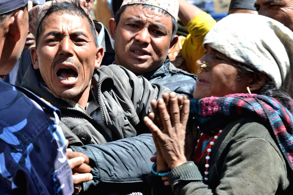 Relatives of victims of a bus accident cry by the site after the bus swerved off the road and fell down in Jumla, Nepal, March 16, 2015. At least 17 people were ...