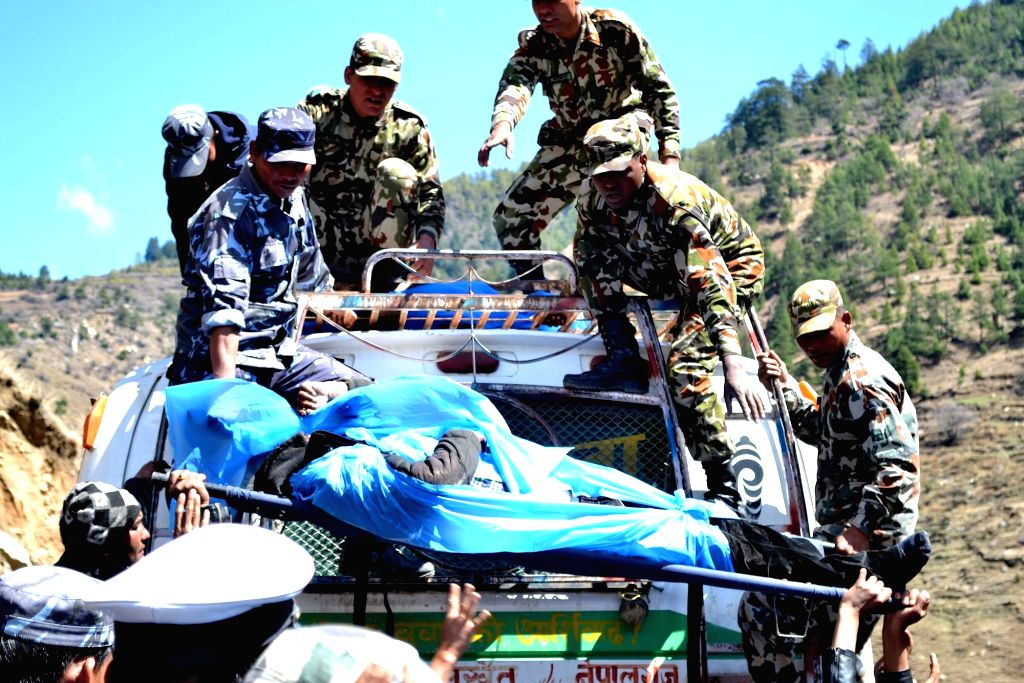 Rescuers carry the bodies of victims of a bus accident after the bus swerved off the road and fell down in Jumla, Nepal, March 16, 2015. At least 17 people were ...