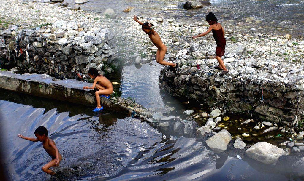 Children are seen playing at Tila River at Tatopani in Jumla of Karnali, Nepal, May 7, 2014.