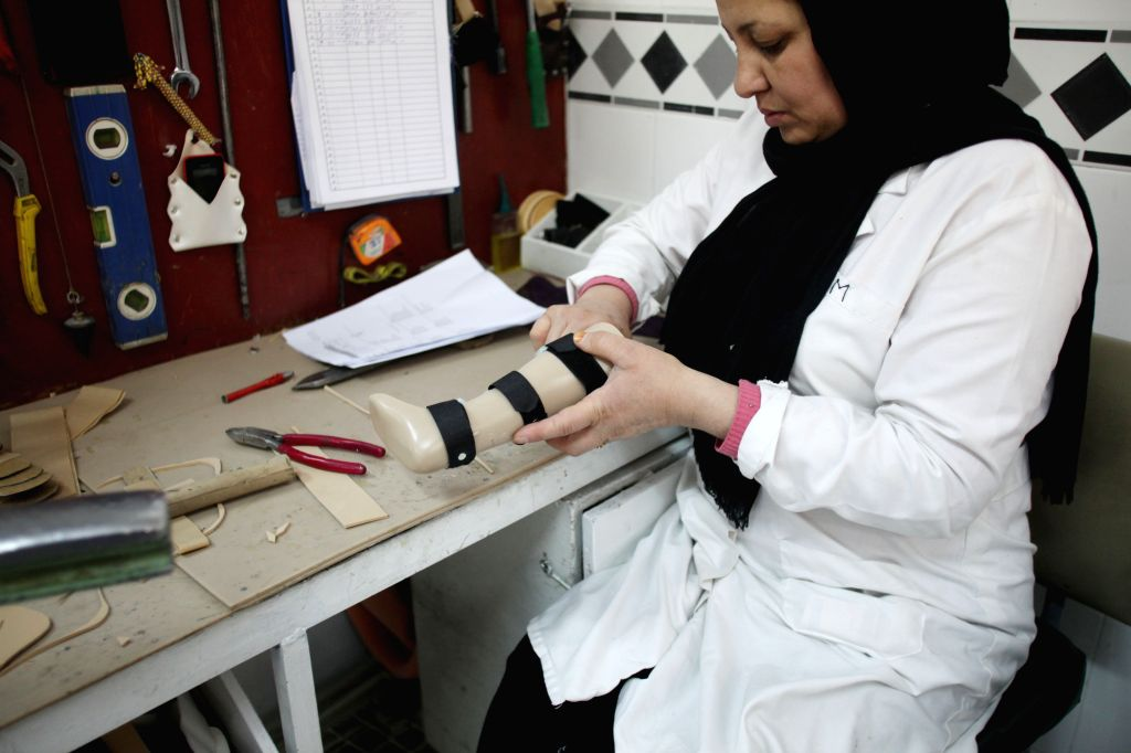 An Afghan woman works on a prosthetic leg at the Orthopedic Center of the International Committee of the Red Cross in Kabul, Afghanistan, Dec. 3, 2014. Taliban militants fighting the ...