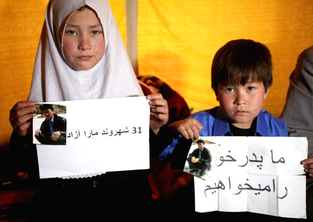 A boy and a girl hold their father's photographs during a sit-in protest near Presidential Palace in Kabul, Afghanistan on April 12, 2015. The protesters have been ...