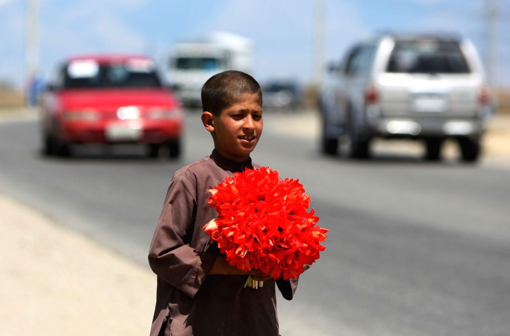 An Afghan child holds fresh flowers for sell along a road in outskirts of Kabul, Afghanistan, on April 17, 2014.