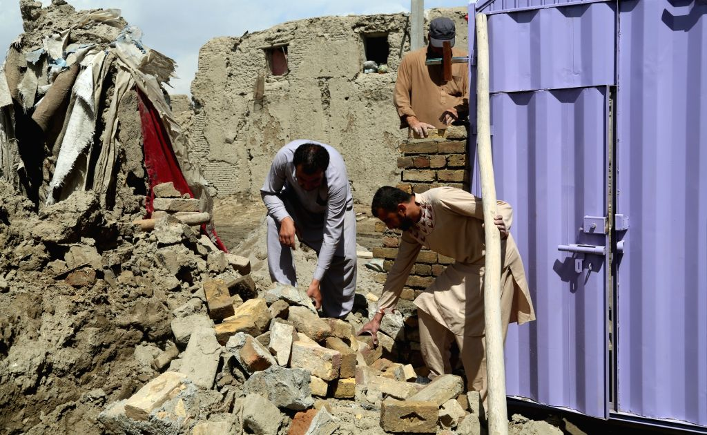 KABUL, April 21, 2016 - Afghan men rebuild the destroyed wall of their house at the site of a truck bombing attack in Kabul, Afghanistan, April 21, 2016. The truck bombing on Tuesday destroyed dozens ...