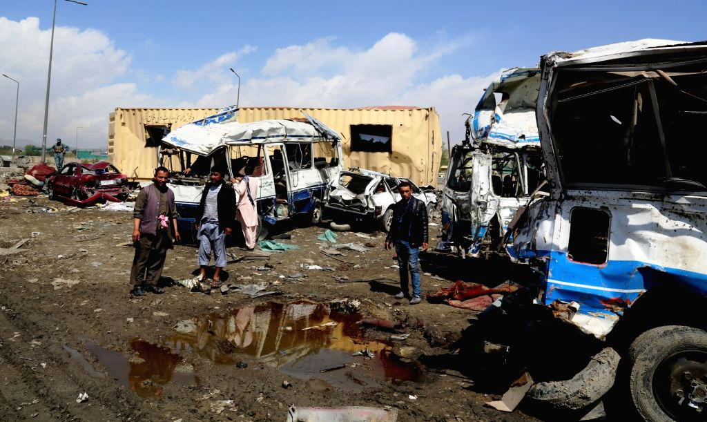 KABUL, April 21, 2016 - Afghan people stand by their destroyed vehicles at the site of a truck bombing attack in Kabul, Afghanistan, April 21, 2016. The truck bombing on Tuesday destroyed dozens of ...