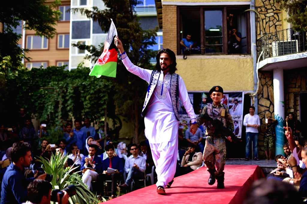 KABUL, Aug. 11, 2017 - Fashion show organizer Ajmal Haqiqi waves a national flag during the show in Kabul, Afghanistan, on Aug. 10, 2017. More than 20 models including six girls attired in colorful ...