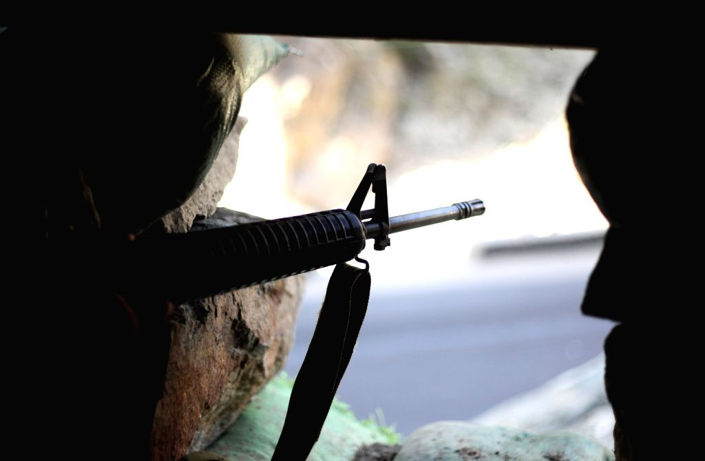 An Afghan National Army soldier keeps watch at a checkpoint on the outskirts of Kabul, Afghanistan, Aug. 6, 2014. Two insider attacks presumably organized by Taliban ..
